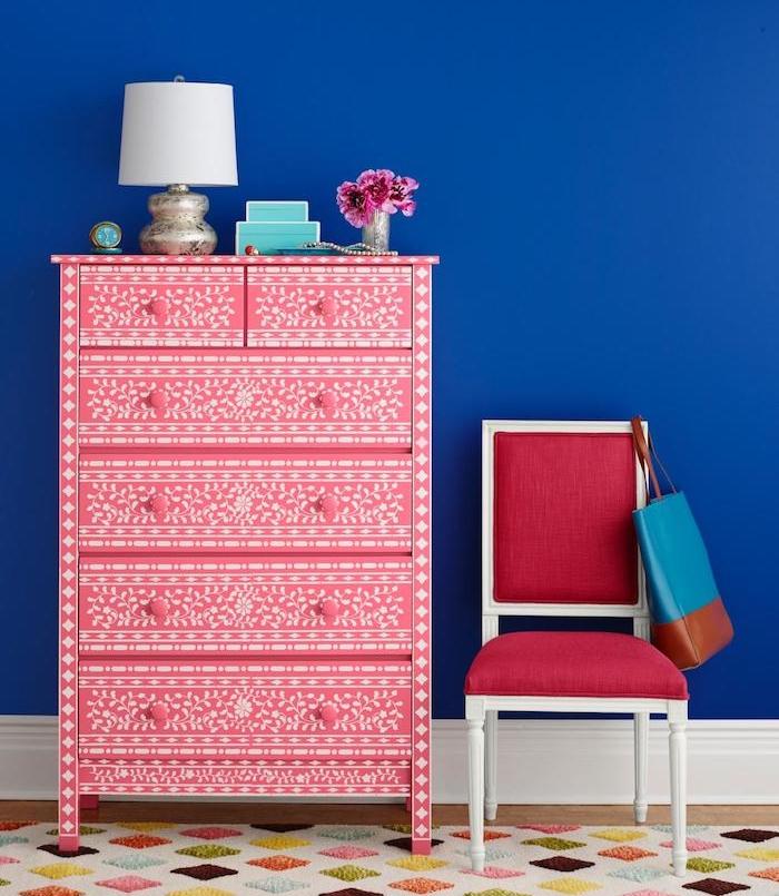 exemple comment customiser un meuble au pochoir, motifs floraux blancs et couleur peinture pour meuble blanche, mur bleu marine, chaise rouge