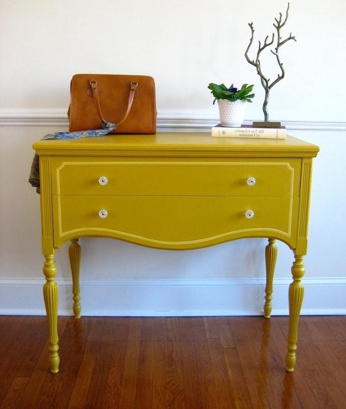 peinture pour meuble jaune, table d appoint repeinte, boutons vintage, sac à manin en cuir, plante verte et livre, parquet marron