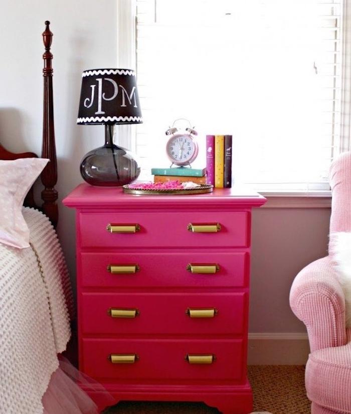 exemple de meuble repeint en rose avec des poignées placard dorées, table de nuit flashy, livres, réveil, lampe de nuit noire, linge de lit rose et blanc