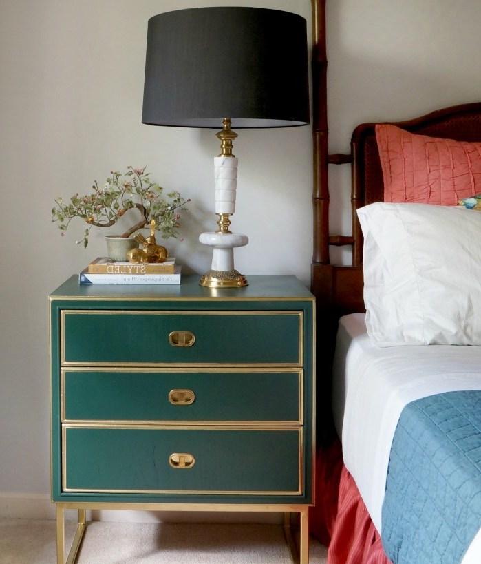 table de nuit avec rangements repeinte en vert émeraude, linge de lit blanc, bleue et rouge, lampe de nuit noire à pied doré, tapis beige