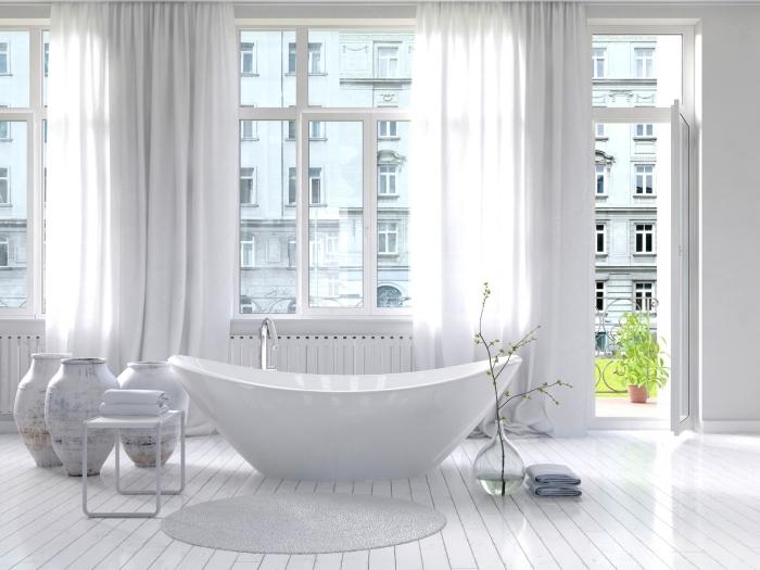 revetement sol, plancher en bois peints en blanc avec tapis rond et gris, salle de bain avec grandes fenêtres et rideaux longs
