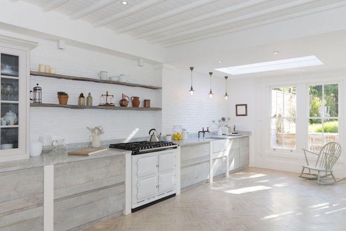 amenagement cuisine rustique blanche avec carrelage blanc, meuble cuisine bois, piano de cuisson blanc, etageres en bois rustiques, chaise à bascule