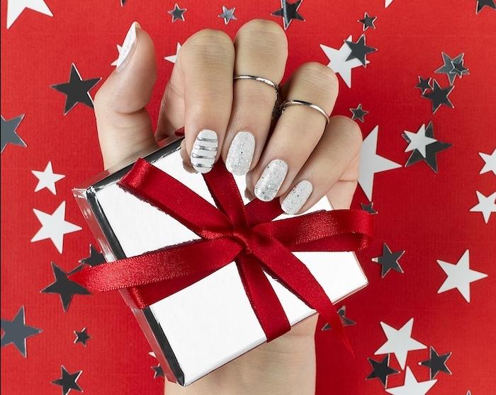 deco ongle noel en blanc avec des motifs argentés, pluie d étoiles et lignes argent, boite a cadeau argent et ruban rouge