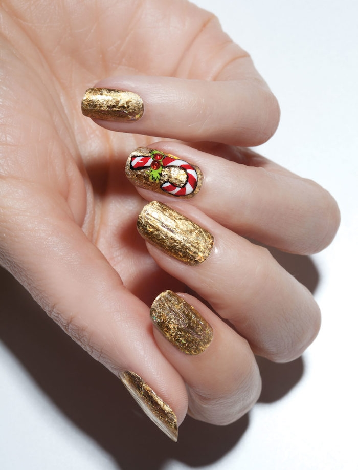 nail art facile de noel, vernis à ongles couleur or et sticker canne de bonbon en roug et blanc sur un ongle