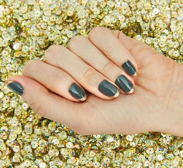 nail art noel facile, vernis à ongles couleur vert de gris avec un bout couleur or, main sur un fond e paillettes dorées
