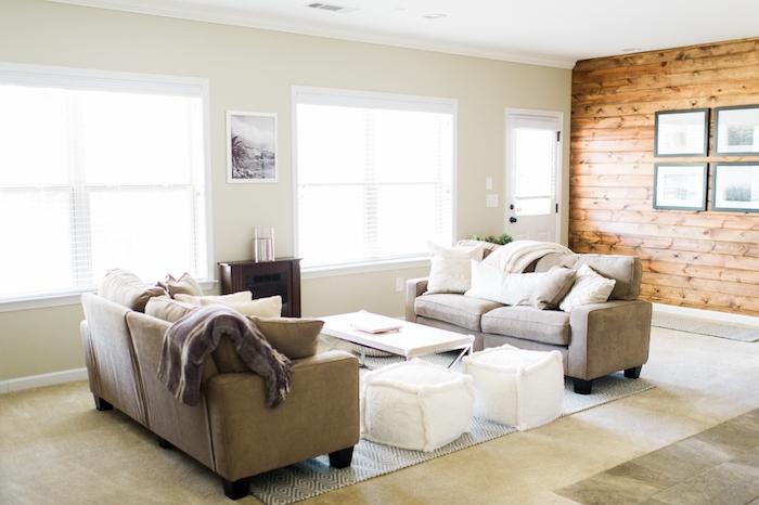 murs couleur gris souris peinture, canapés gris, tapis grege, tabourets et cubes de tissu blancs, cheminée marron, mur de poutres en bois