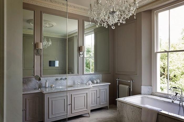 mur couleur gris clair avec meuble cuisine gris et plan de travail marbre, baignoire à poser, lustre baroque, miroirs