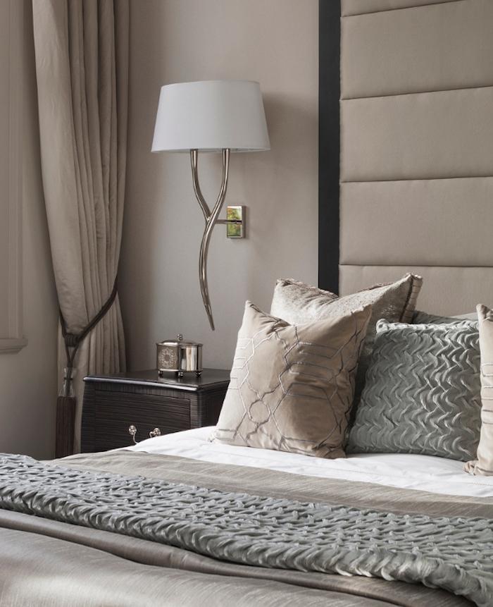 mur peinture gris perle, lit gris et linge de lit gris et marron, lampe blanche, table de nuit avec tiroirs en bois marron