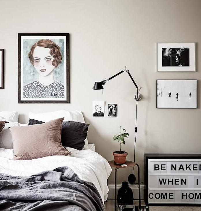 chambre à coucher couleur taupe clair, linge de lit gris anthracite et blanc, coussin marron, murs couleur gris perle, nuance grege, deco murale dessin portrait