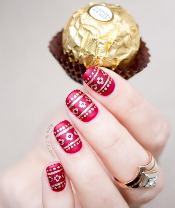 nail art rouge de noel, vernis à ongles rouge et motifs dorés, fleurs, pois et lignes couleur or, bonbon ferrero rocher