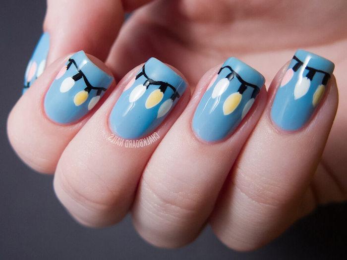 ongle noel bleu avec dessin de motif guirlande lumineuse à ovales colorés en rose, blanc et jaune