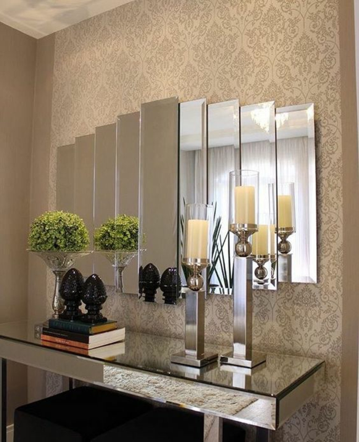 quelle couleur pour le couloir papier peint couloir finition satinée en nuances beiges, miroir large composé de petits miroirs avec des jeux de lumière et d'images, table rectangulaire avec surface miroir brillante, deux bougeoirs en métal couleur argent avec des bougies couleur crème