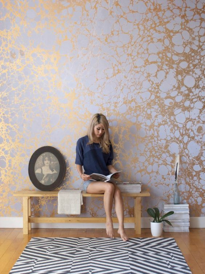 papier peint couloir idée entrée en couleur bleu pastel et des effets bronzés, tapis carré en noir et blanc, portrait photographique de femme en cadre noir en forme ovale, banc en bois clair, petit pot blanc avec plante exotique verte, parquet finition lisse et brillante en jaune