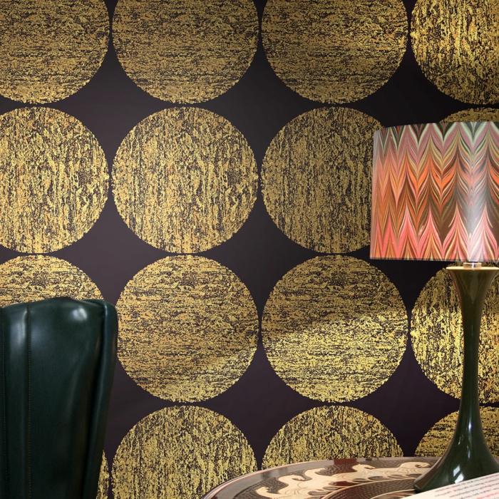 papier peint trompe l'oeil avec des grands cercles en couleur or sur un fond prune, grand fauteuil faux cuir en noir, avec lampadaire de table à abat-jour aux motifs abstraits style années 70
