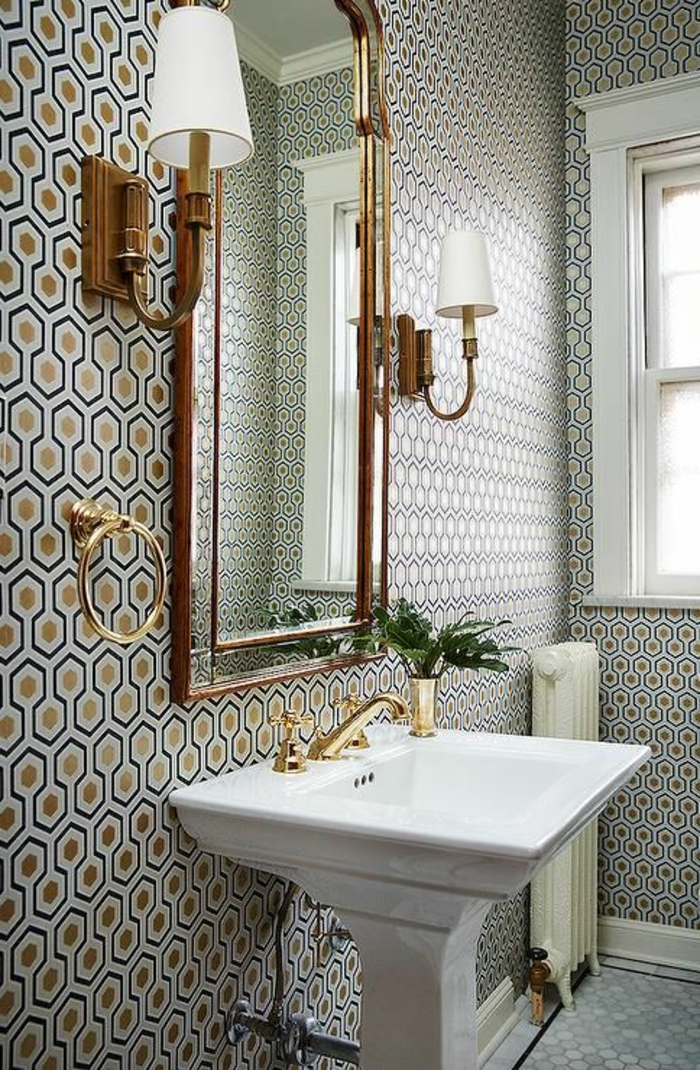 papier peint liberty en couleur bleu marine et or, aux motifs ruches, dans une salle de bains en style classique, avec grand lavabo blanc en style vintage, deux lampadaires appliques muraux avec des abat-jours blancs