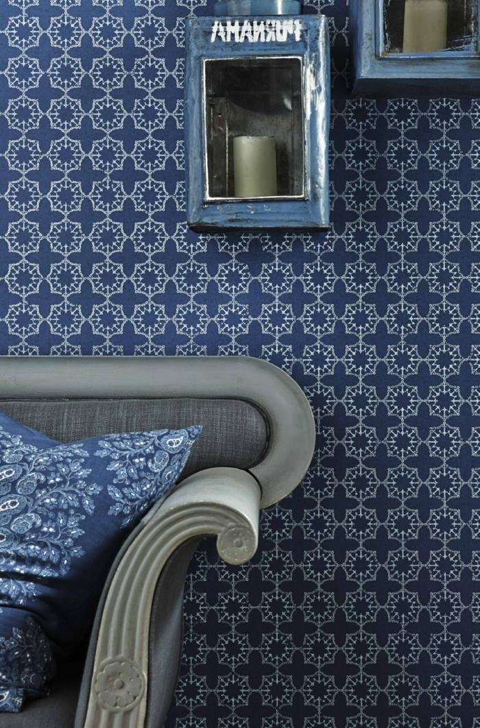 papier peint trompe l'oeil en bleu et blanc, papier peint geometrique, salon avec canapé en gris clair avec des coussins en bleu et blanc, style chinois, étagères en métal bleu avec des grandes bougies grises