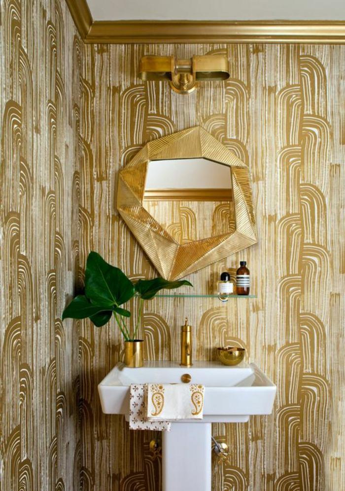 papier peint trompe l'oeil en couleur or avec des motifs géométriques, salle de bains avec lavabo vintage blanc, miroir excentrique aux formes irrégulières avec cadre imitation or massif, plafond en blanc, encadré avec frises massives imitation or