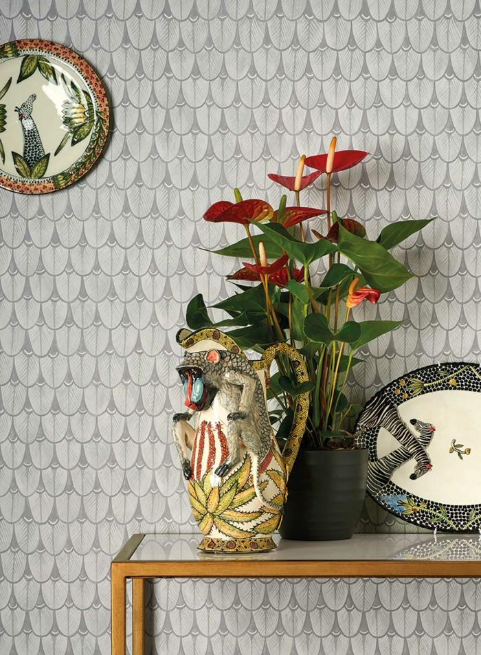 papier peint trompe l'oeil en gris clair, avec table rectangulaire en métal couleur or, porcelaine chinoise décorative, pot noir avec une plante verte fleurie, chat décoratif en porcelaine en noir, rouge et jaune