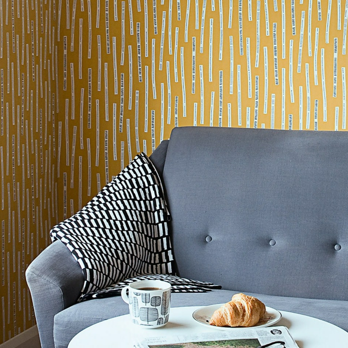 papier peint intissé en jaune et blanc, avec des messages humoristiques, canapé en velours bleu pastel, petite table ronde et blanche avec un croissant et un café