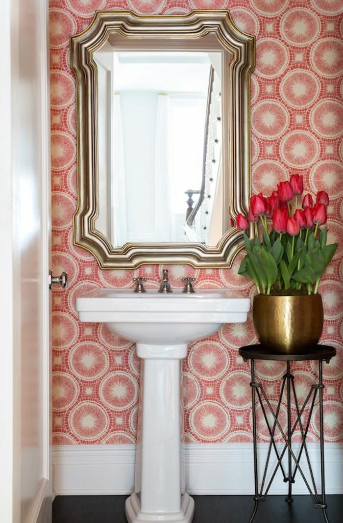 poster geant en couleur corail et blanc, lavabo vintage, sol noir finition brillante, grand miroir rectangulaire en style baroque, petite table ronde en métal noir avec un vase en métal couleur or rempli de roses rouges