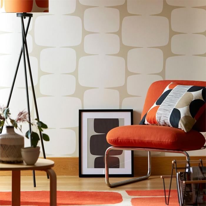 papier peint trompe l'oeil en beige et blanc, sol en orange et blanc, fauteuil en métal blanc, avec deux grands coussins en orange, tableau posé par terre en noir et blanc, cadre noir, coussin sur le fauteuil avec des formes géométriques rondes en orange, noir, blanc et beige