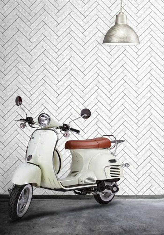 papier peint trompe l'oeil aux motifs briques blanches dans l'entrée d'un appartement, luminaire suspendu en métal couleur argent en style industriel, sol recouvert de moquette grise finition veloutée