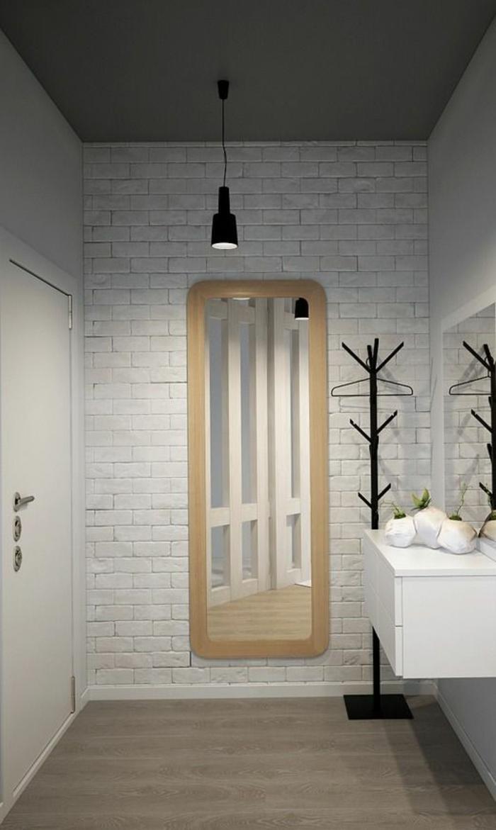 papier peint intissé dans l'entrée d'une maison, motifs briques blanches, lampadaire suspendu en métal noir, meuble pour suspendre les vestes en métal noir , meuble suspendu en blanc, sol couleur taupe, miroir au cadre blanc