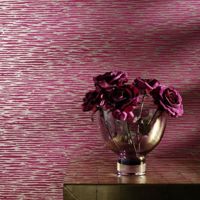 papier peint trompe l'oeil en rose et blanc, motifs zébrés, table avec plan brillant en couleur or, vase en verre blanc transparent avec des roses en couleur bordeaux, ambiance raffinée de luxe