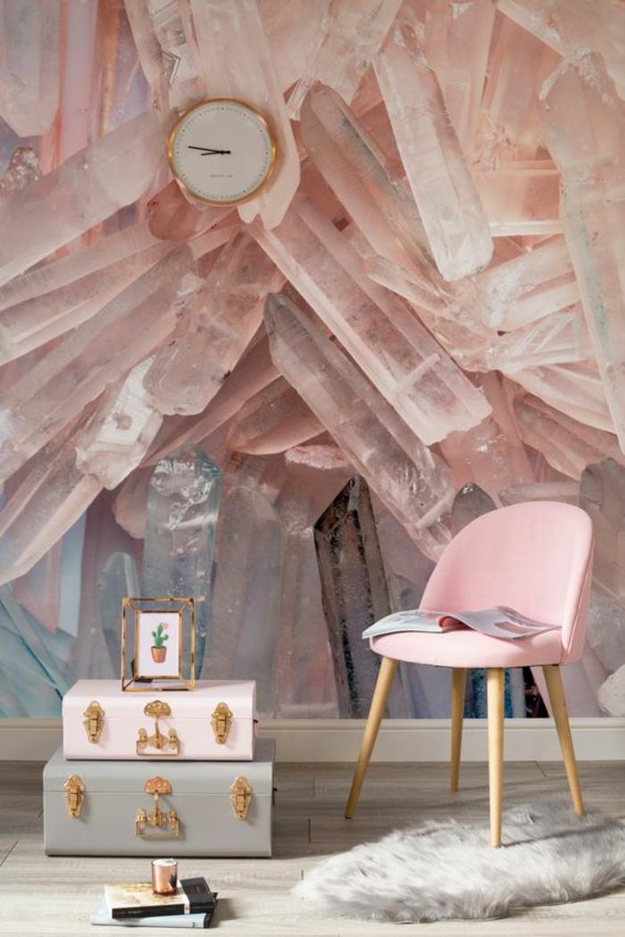 papier peint trompe l oeil avec des motifs cristaux roses, deux malles de rangement en bleu pastel et en blanc, chaise en rose et pieds en bois clair, parquet gris, petit tapis en fausse fourrure blanche