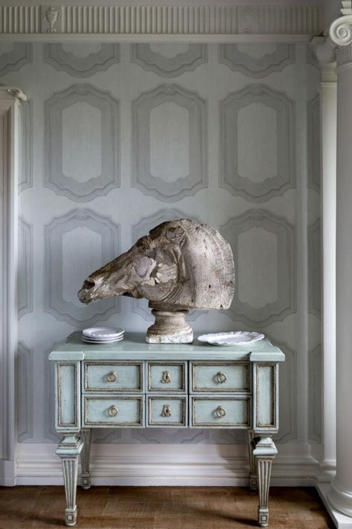 papier peint imitation pierre,entrée de luxe, meuble en vert menthe en style shabby chic avec une grande tête de cheval dessus et des plats de porcelaine blancs, sol recouvert de parquet en marron clair