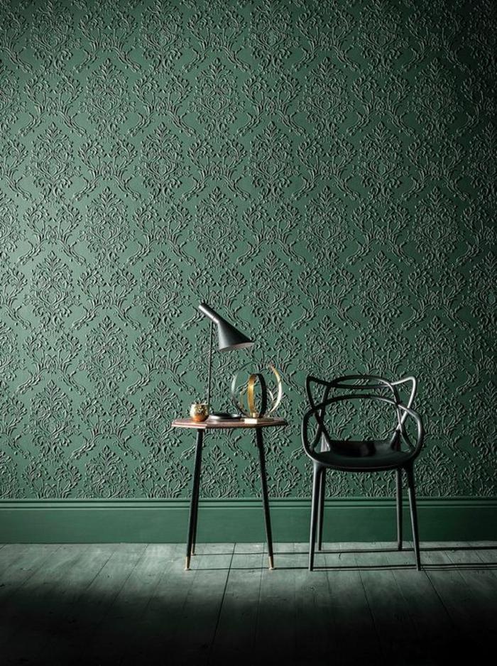 papier peint trompe l'oeil en vert, aux motifs arabesques, avec chaise en métal noir et table ronde avec des pieds hauts en métal noir, lampadaire pour table en métal noir et style industriel