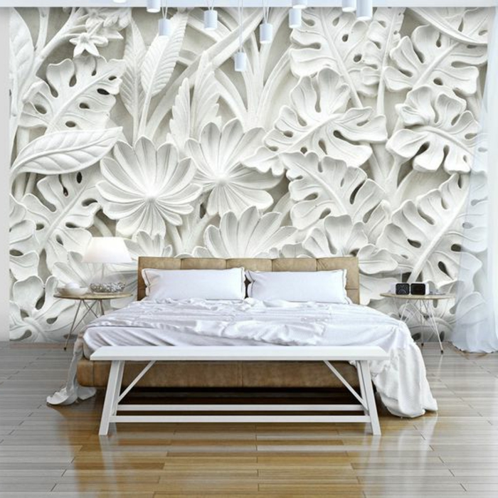 papier peint intissé en blanc, aux motifs grandes feuilles de palmier, chambre d'adulte avec grand lit matrimonial pliant en beige, petite table de chevet ronde, parquet clic-clac en beige clair