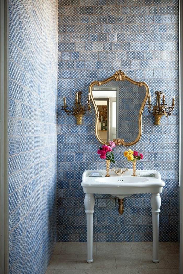 papier peint trompe l'oeil dans une salle de bains en style classique, avec miroir en forme baroque au cadre en métal couleur or, avec deux appliques murales en forme de bougeoirs, en style château, mur en bleu et blanc, effet de mosaïque à l'ancienne