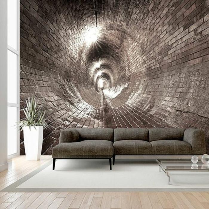 papier peint trompe l'oeil en forme de spirale en mur en briques en couleur bronze, salon avec tapis en gris clair avec les bords en gris foncé, canapé en vert épinards, petite table basse carrée en verre trempé, grand pot blanc avec une plante verte de type palmier