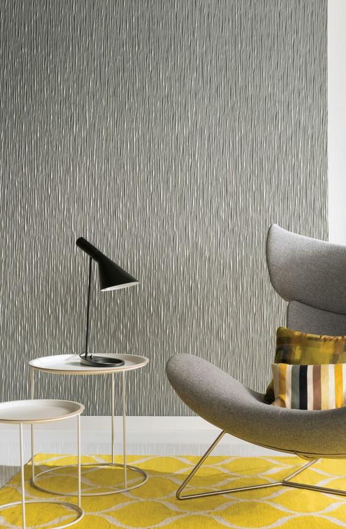 papier peint imitation lambris, en couleur grise, salon avec tapis en jaune et blanc aux motifs arabesques, fauteuil en gris clair, deux petites tables rondes en métal blanc avec un luminaire en métal noir en style industriel