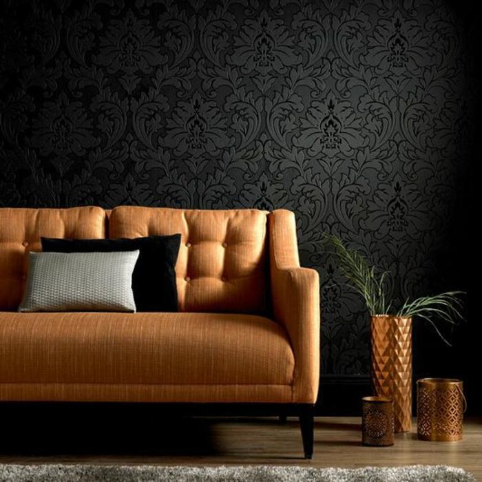 papier peint intissé en noir aux motifs arabesques, avec effet 3 D, canapé en beige, pot avec plante verte et vase en couleur bronze avec des motifs triangulaires en relief