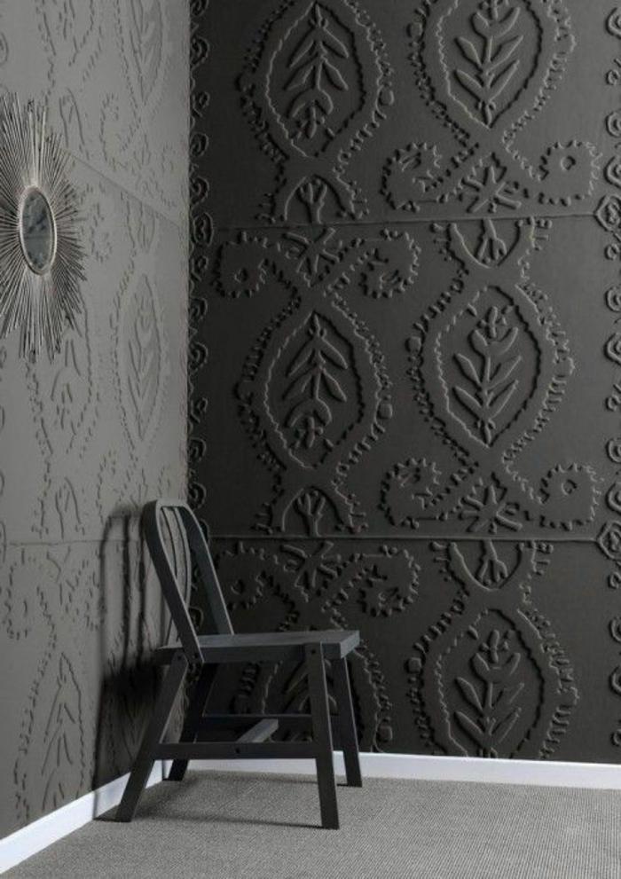papier peint trompe l'oeil, murs en gris foncé, aux motifs ornements en fleurs et feuilles, miroir sorcière en forme de soleil au mur, tapis gris au sol