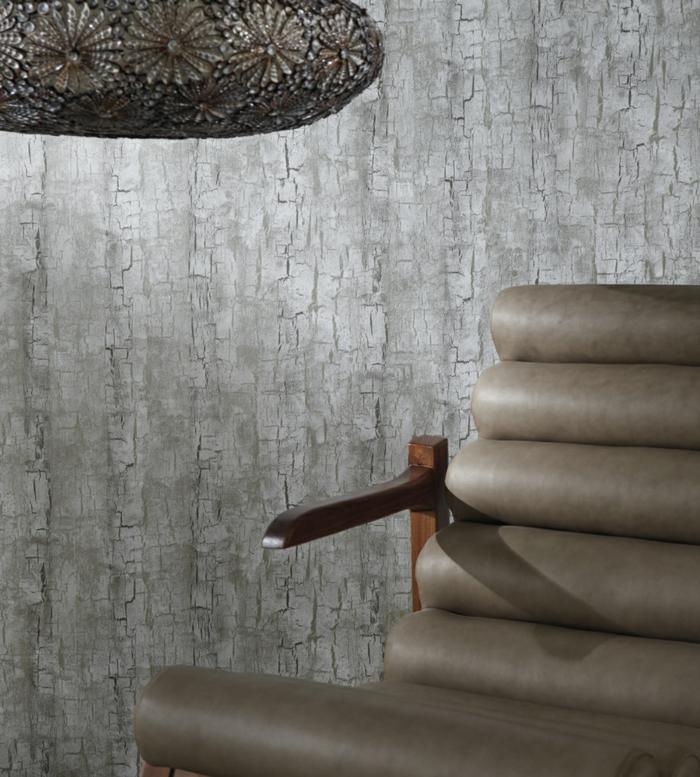 """papier peint imitation lambris, papier peint trompe l'oeil, motifs écorce d'arbre en couleur grise, fauteuil en couleur taupe en faux cuir aux effets """"bonhomme Michelin"""""""