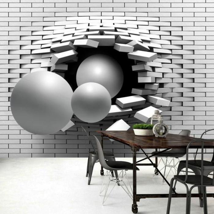papier peint trompe l'oeil avec effet 3 D, 3 grandes boules qui brisent un mur en briques blanches, effet réaliste, table à rouleaux avec plan en marron foncé, cinq chaises en couleur grise