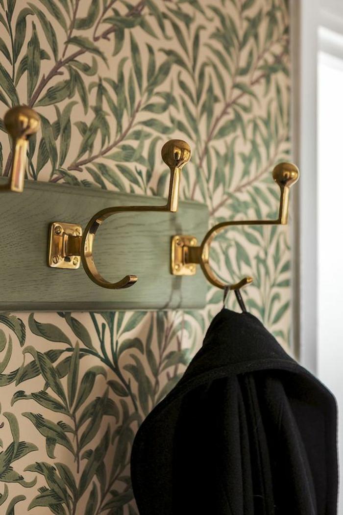 papier peint trompe l'oeil aux motifs feuilles vertes de plantes, mur d'une entrée, cadre de porte blanc, avec porte-manteau vintage en bois réséda et éléments en métal doré avec des grandes boules brillantes