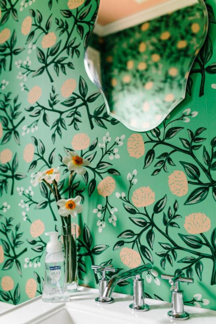 papier peint liberty en réséda et beige, avec miroir sans cadre en formes baroques, lavabo vintage blanc, vase en verre transparent avec trois fleurs, ambiance néo classique
