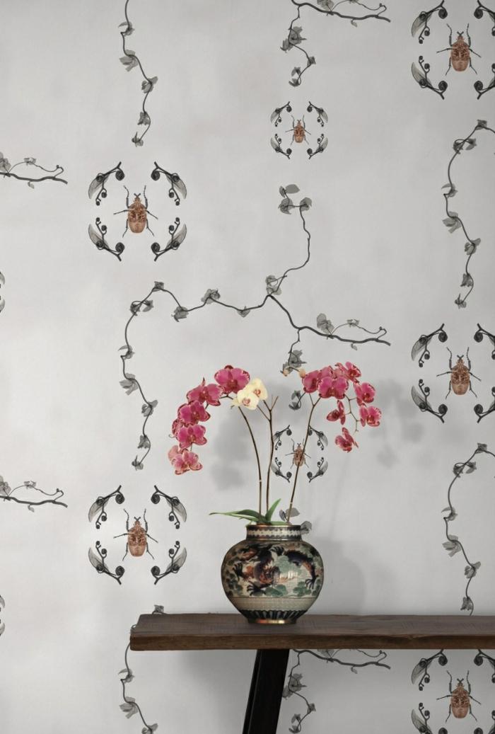 papier peint trompe l'oeil aux motifs insectes et feuilles, mur d'entrée avec table minimaliste avec vase bombée aux motifs chinois, avec des fleurs en rose et blanc