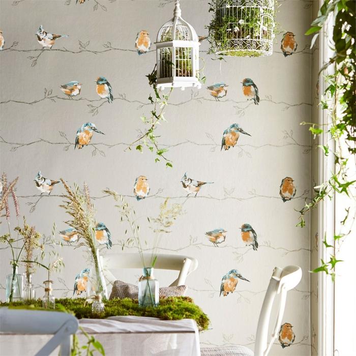 poster geant papier peint trompe l'oeil avec des oiseaux perchés sur des feuilles fines en couleur grise, deux cages à oiseaux suspendues au plafond, des plantes vertes rampantes dans un pot tout près de la fenêtre, chaises blanches autour d'une table ronde