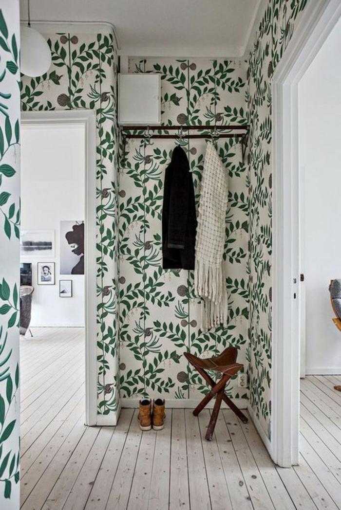 papier peint trompe l'oeil dans une entrée, avec des plantes vertes rampantes, plafond en blanc, porte-manteaux en métal noir