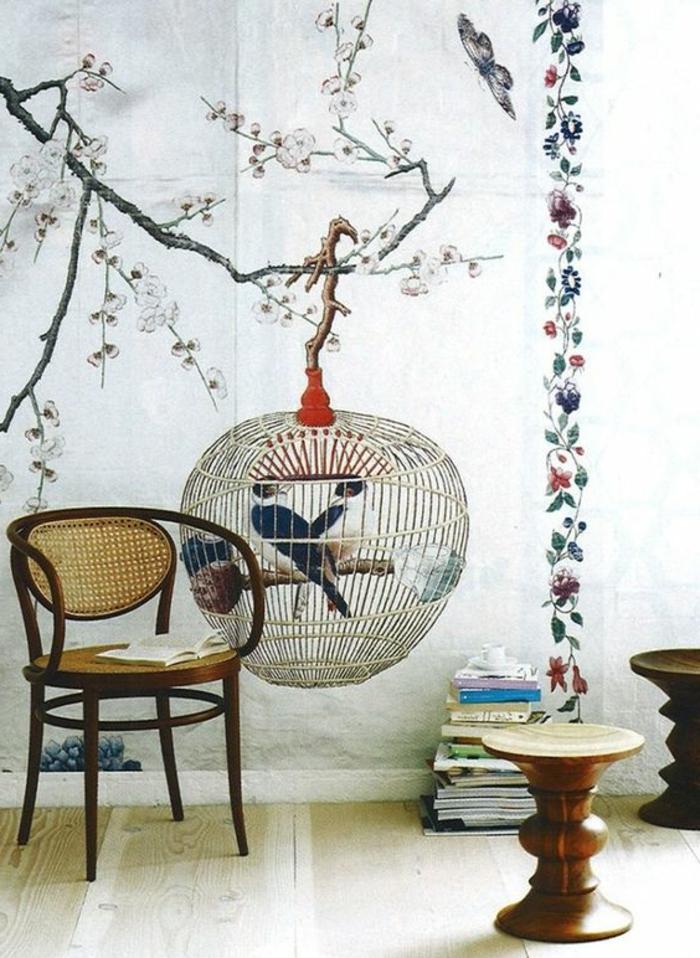 papier peint trompe l'oeil avec motif grande cage d'oiseaux perchée sur un arbre, cerisier fleuri en fleurs roses délicates, chambre avec chaise en style asiatique, deux tabourets en bois clair et foncé, parquet en blanc et beige