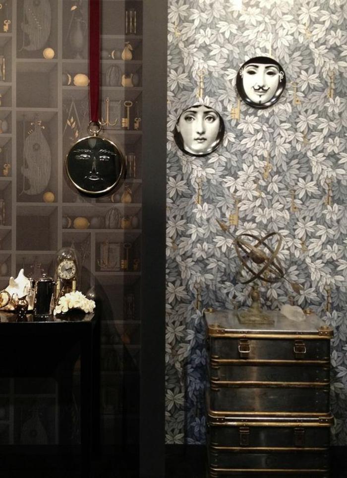 papier peint trompe l'oeil, feuilles blanches et grises, trois photographies en cadres ronds au mur, meuble en métal avec objet décoratif, meuble en bois noir