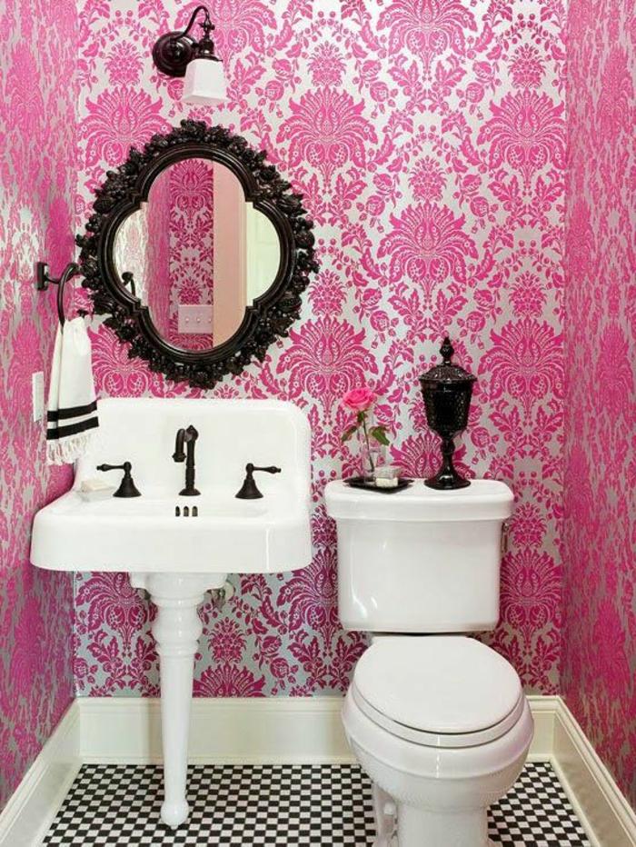 papier peint trompe l'oeil en rose et blanc, aux motifs arabesques, salle de bains avec miroir baroque en bois noir, applique en métal noir et abat-jour en blanc, lavabo blanc en style vintage, carrelage en noir et blanc aux motifs d'échiquier
