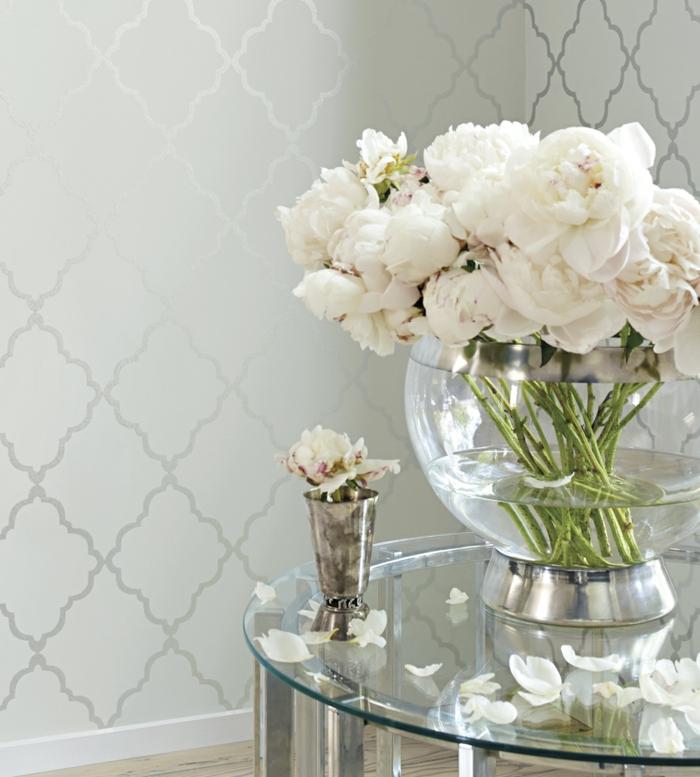 papier peint trompe l'oeil papier peint liberty en gris satiné, grand bol en verre blanc transparent avec des roses blanches, petite table basse en verre blanc en forme ronde, avec des pieds en métal couleur argent, parquet gris