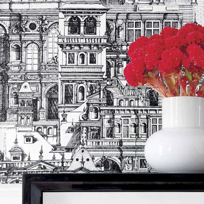 poster geant aux motifs édifice du XIX-ème siècle de style néo-classique, grand vase blanc moderne avec des fleurs d'œillet rouges, table basse noire