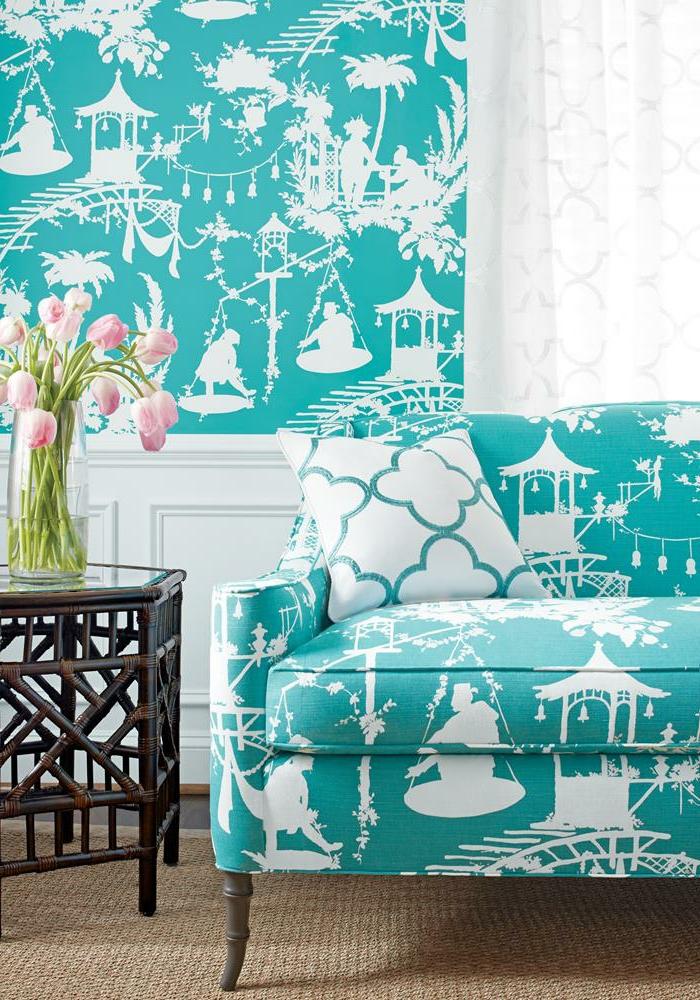 papier peint trompe l'oeil aux motifs asiatiques chinois blancs sur fond de couleur turquoise bleue, motifs repris sur le fauteuil en tissu, coussin en bleu et blanc, petite table en bois marron, moquette en relief léger en beige